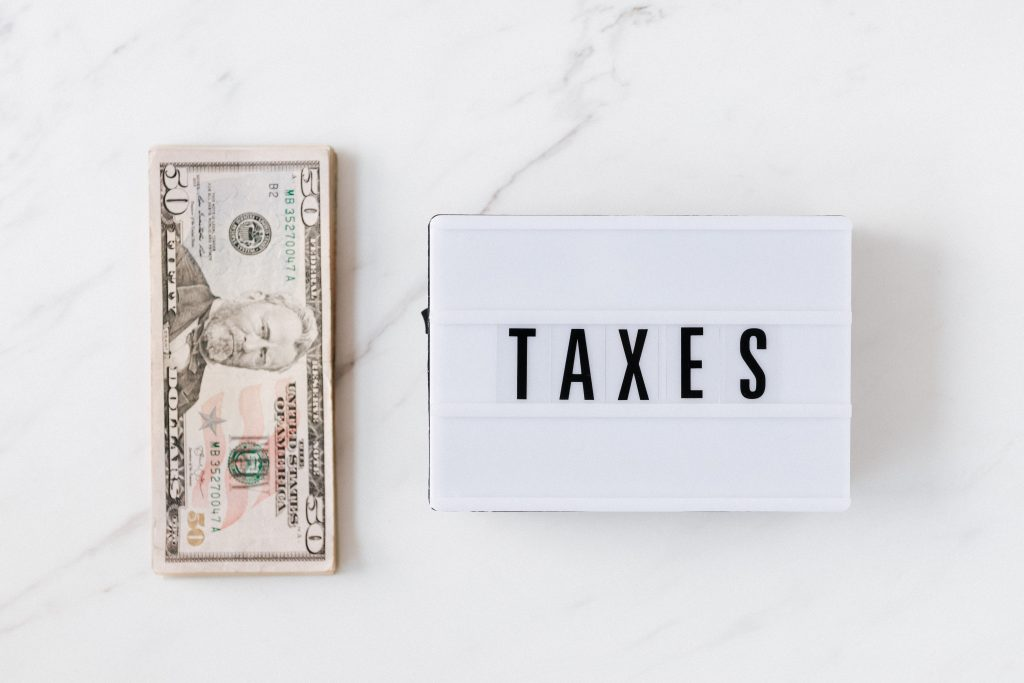 dollar bill and taxes sign