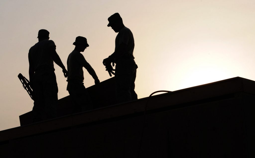 silhouette builders under a white sky